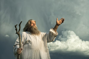 An old man with long grey hair and a long grey beard standing in front of a dramatic dark sky. He is wearing a white toga and holding a wooden bar. His arm is stretched out for giving a sign or for blessing and he is looking up to the sky.